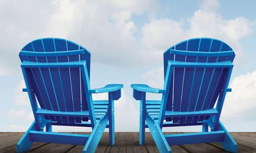 pair of blue Adirondack chairs on wooden deck facing blue sky