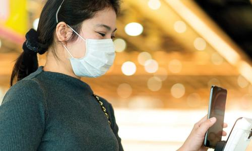 young Asian woman wearing mask holds smartphone up to payment kiosk at store