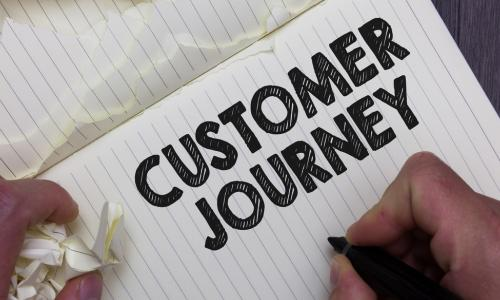 notebook with customer journey written on page