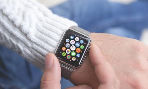 person in white sweater checking Apple Watch displaying colorful icons