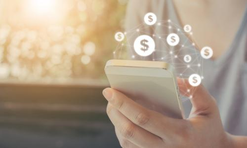 person using smartphone with dollar signs floating