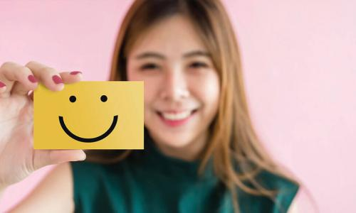 smiling young Asian woman in green shirt holds up yellow notecard with a smiley face drawn on it