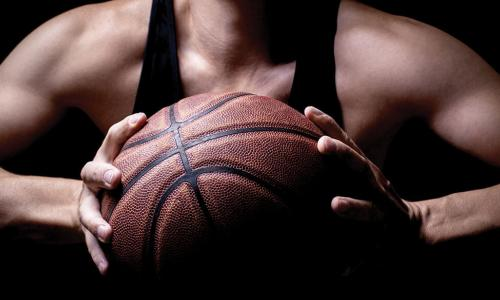 muscular athlete holding basketball in both hands preparing to pass