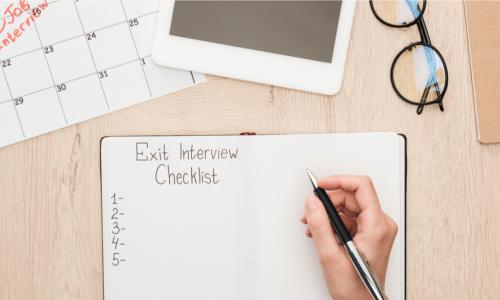 partial view of recruiter holding pen near notebook with exit interview checklist lettering