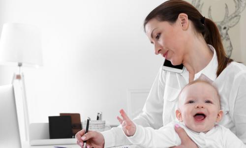 professional mom working from home while holding laughing baby