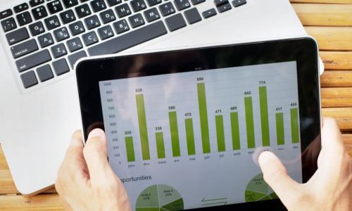 hands on tablet with charts