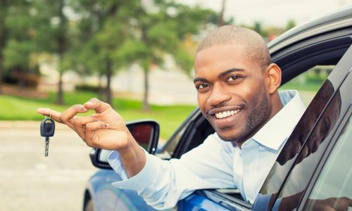 man in blue car leaning out window with key