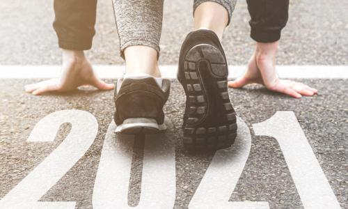 runner in black sneakers crouched at 2021 starting line