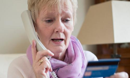 senior woman giving credit card information on phone