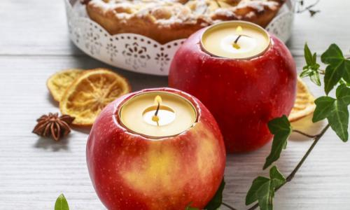 tea candles set into hollowed out apples sitting on a white wood table in front of a pie