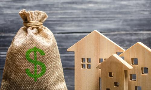 burlap bag with green dollar sign on it next to wooden houses