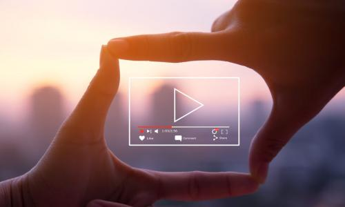 person forming camera frame with fingers with digital illustration of a video player in the frame