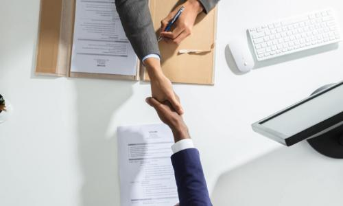 high-angle shot of two businesspeople shaking hands across a table