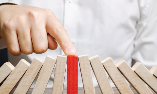 businessman reaches out finger to stop red wooden block from falling while propping up the fallen wooden blocks around it