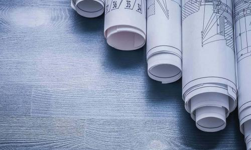 rolled up architectural blueprints on wooden table