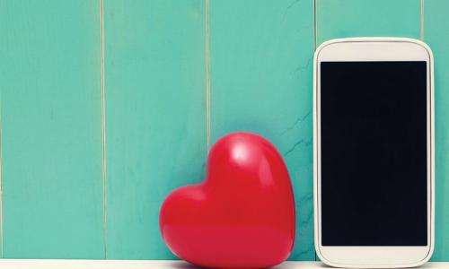white smartphone next to shiny red heart in front of green wooden wall