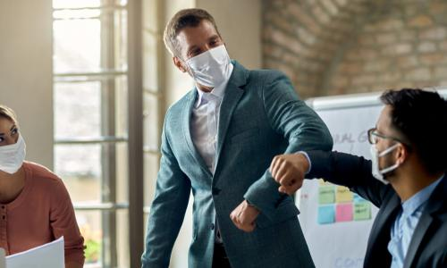 description businessmen do an elbow bump in masks at meeting with another businesswoman
