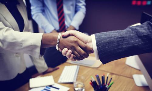 handshake of Black businesswoman and white businessman