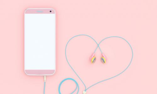 pink smartphone with earbud headphone cord curled into a heart shape
