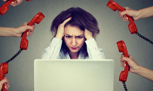 stressed businesswoman holding head while working on laptop surrounded by hands holding out many red telephone receivers