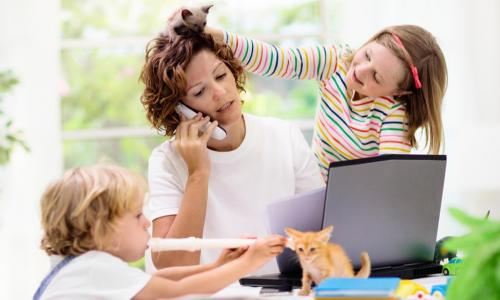 mother working from home on laptop and phone with two young children and kittens playing around her