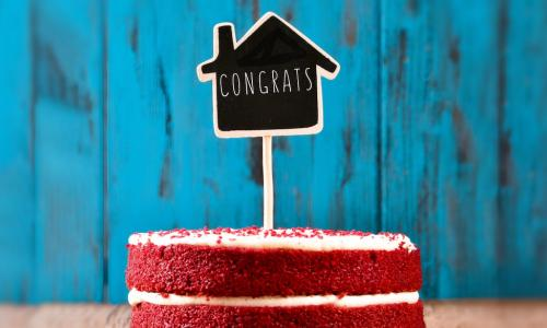 chalkboard congrats sign in shape of house stuck into a celebratory red velvet cake