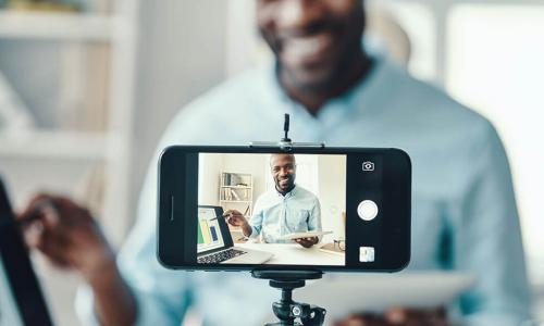 smartphone camera on tripod filming smiling Black businessman presenting a chart to viewers