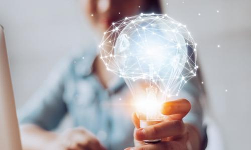 woman at desk holding out a glowing lightbulb with a network of data points forming the image of a brain on top of it