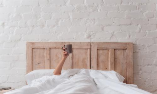 woman's hand sticking out of white bed covers holding cup of coffee