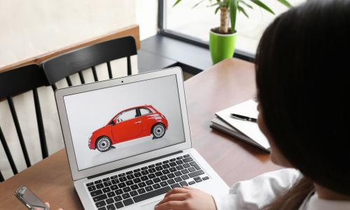 woman using a laptop and a phone to do car shopping